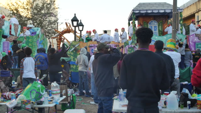 Mardi Gras revelers party in the street during the Krewe of Thoth Things with Wings themed parade as floats pass on St Charles Avenue near the...