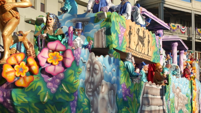 Mardi Gras revelers put their hands up for beads as a Krewe of Thoth Things with Wings Winged Gods themed parade float passes Lee Circle