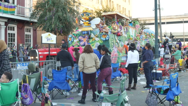mardi gras revelers watch as a krewe of thoth things with wings bees themed parade float passes - gras stock videos and b-roll footage