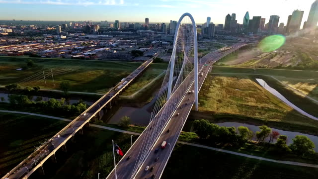 Margaret Hunt Hill Bridge spanning across the Trinity River in Dallas Texas During Sunirse circling around bridge