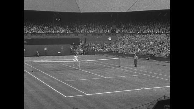 VS Margaret Osborne duPont and Doris Hart walk across court and stand with bouquets at Wimbledon women's singles match / match between duPont and...