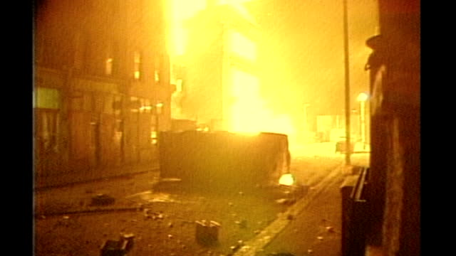 vídeos de stock, filmes e b-roll de report from brixton s29031001 april 1981 police behind riot shields pan to burning building and vehicle close shot burning vehicle in road police... - brixton