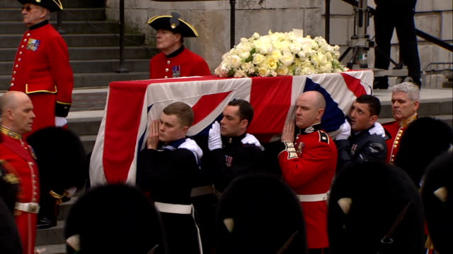 Margaret Thatcher funeral 1000 1100 Floral tribute on coffin PULL OUT / Military pallbearers along and lifting coffin off carriage / floral tribute /...
