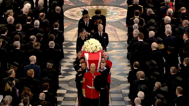 1100 1200 **Choral music over following** Coffin carried along aisle past Queen Elizabeth and Prince Philip/ close shots of coffin and pallbearers as...
