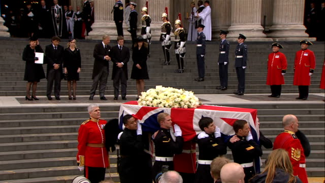 margaret thatcher funeral: 12.00 - 12.30; ext members of the clergy down steps from the cathedral followed by soliders carrying coffin as bells ring... - mourner stock videos & royalty-free footage
