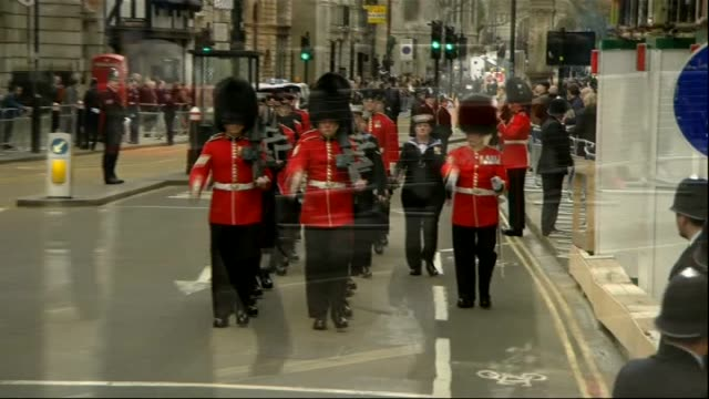 margaret thatcher funeral: funeral procession: fleet street; coldstream guards marching on road / people looking out from upper windows of buildings... - fleet street stock videos & royalty-free footage