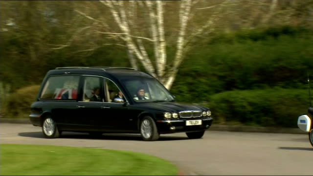 Hearse in crematorium grounds ENGLAND London Mortlake EXT Hearse along in crematorium / hearse parking / Thatcher family members standing at rear of...