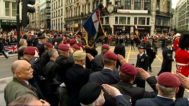 london crowds / protesters england london ext baroness thatcher unionjackdraped coffin on gun carriage along in military funeral cortege on journey... - saluting stock videos and b-roll footage