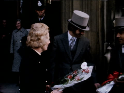 Margaret Thatcher is presented with bouquets of flowers as she leaves the Houses of Parliament after winning the Tory leadership vote 1975