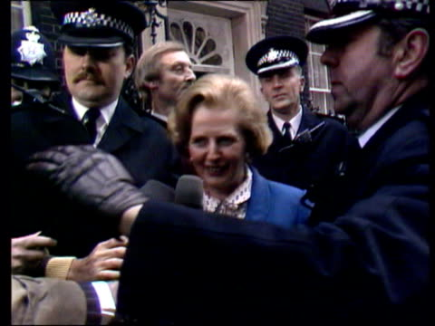 vidéos et rushes de margaret thatcher mp arrives to take office car driving down downing street large cheers and some boos heard / thatcher out of car wearing blue suit... - 1979