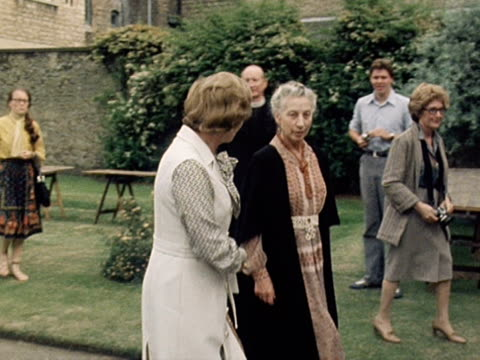 margaret thatcher walks through the gardens of somerville college with a don during the colleges centenary celebrations - centesimo anniversario video stock e b–roll