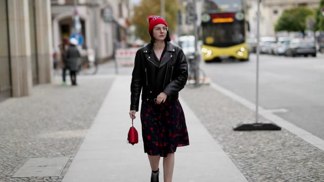 maria barteczko wearing red beanie from gucci teale cherry printed dress from realisation par black biker leather jacket from acne studios red mini... - motorradfahrer stock-videos und b-roll-filmmaterial