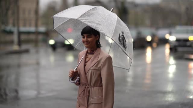 vídeos y material grabado en eventos de stock de maria bernad wears a pink long coat, a bottega veneta cream color puff bag, a turtleneck brown dress, during paris fashion week - womenswear... - paraguas