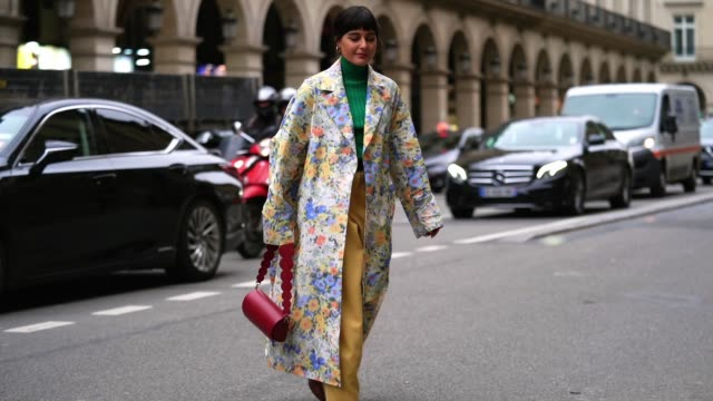 maria bernad wears earrings, a green wool turtleneck pullover, a long floral print colored trench coat, a burgundy leather bag, a belt, yellow flared... - street style stock videos & royalty-free footage