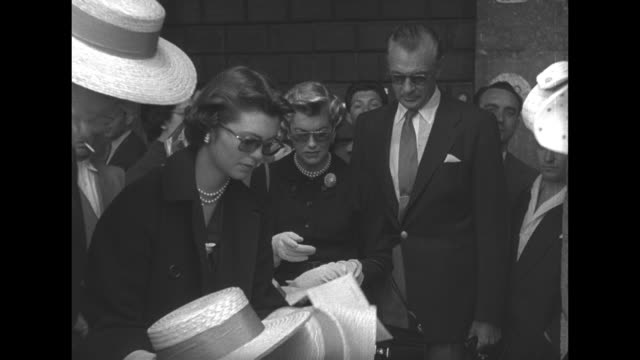 maria cooper chooses straw hats from several on table as her parents, actor gary cooper and his wife veronica look on / gondolier places straw boater... - straw hat stock videos & royalty-free footage