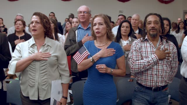 Maria Elena and others become American citizens during a US Citizenship Immigration Services naturalization ceremony at the Hialeah Field Office on...