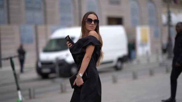 stockvideo's en b-roll-footage met maria rizzo wears earrings sunglasses a black offtheshoulder dress a black yves saint laurent clutch black sued kneehigh boots with shiny gold end... - oorbel