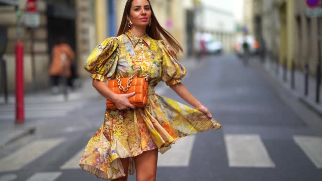 maria rosaria rizzo wears golden earrings, a yellow short flowing ruffled dress / shirt with puff sleeves and floral print from leo&lin, an... - dress stock videos & royalty-free footage
