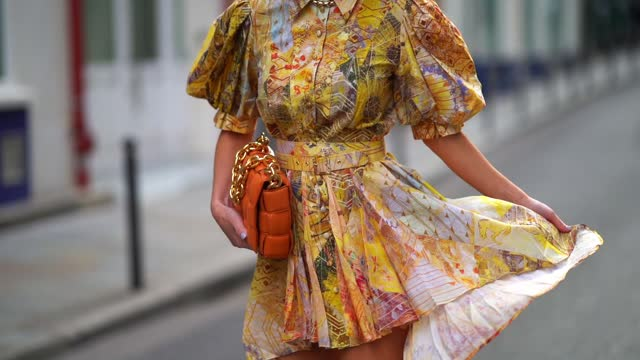 maria rosaria rizzo wears golden earrings, a yellow short flowing ruffled dress / shirt with puff sleeves and floral print from leo&lin, an... - floral pattern stock videos & royalty-free footage