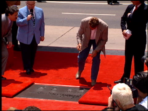 vidéos et rushes de maria shriver at the dedication of arnold schwarzenegger's footprints at grauman's chinese theatre in hollywood california on july 14 1994 - arnold schwarzenegger