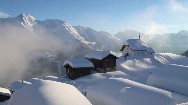 maria zum schnee chapel with snow-covered log cabins in the famous village bettmeralp with dramatic clouds. - 山小屋点の映像素材/bロール