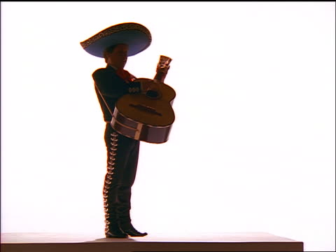 SILHOUETTE mariachi band musician playing guitar / white background
