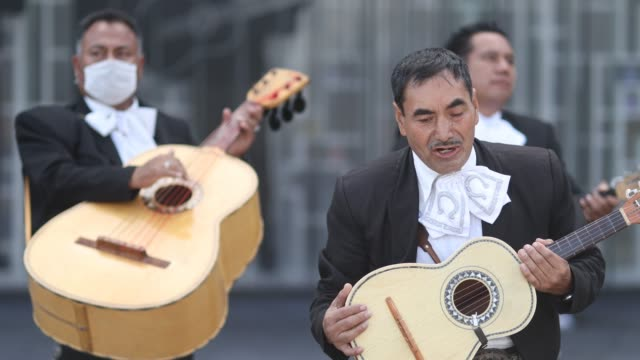 mariachi musician plays the guitarrón guitar wearing a protective mask while another member sings as the band maricahi cultural perform during a... - cactus stock videos & royalty-free footage