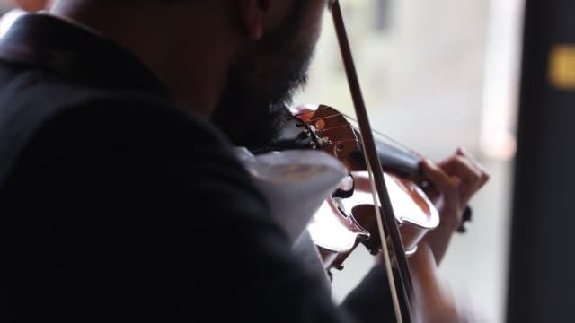 vídeos de stock e filmes b-roll de mariachi musician plays the violin as the band maricahi cultural perform during a recording at the museo del tequila y el mezcal as the coronavirus... - violino