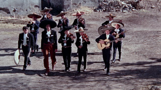 mariachi playing and walking through town looking forward approaching a house to serenade a woman - mexican ethnicity stock videos & royalty-free footage