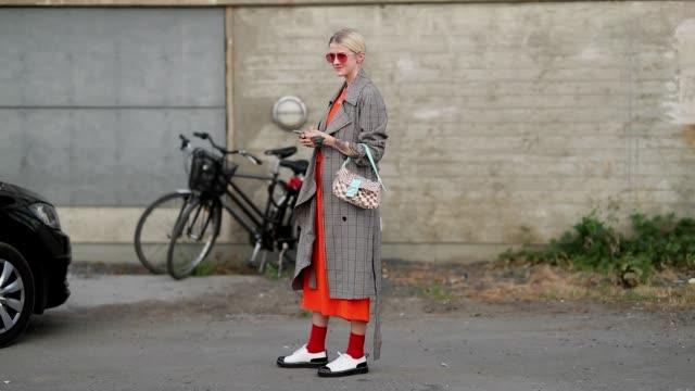 Marianne Theodorsen wearing orange dress checked coat Fendi bag red socks is seen outside Ganni during the Copenhagen Fashion Week Spring/Summer 2019...