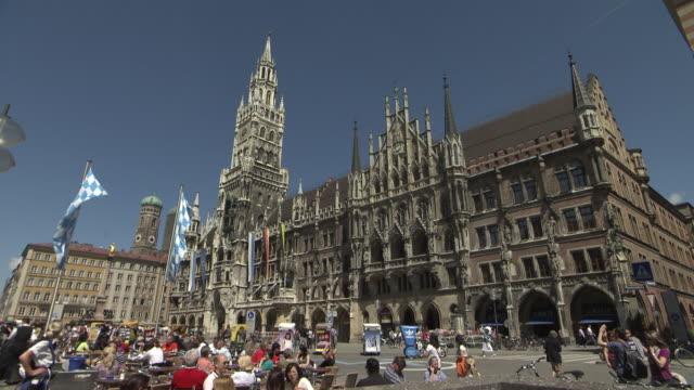 Marienplatz, city hall with flags, blue sky, people