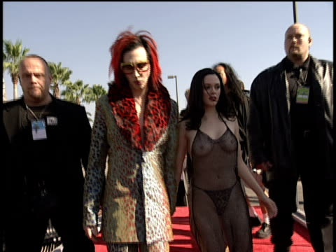 stockvideo's en b-roll-footage met marilyn manson and rose mcgowan who is wearing a see through dress arriving and posing for pictures on the red carpet - 1998