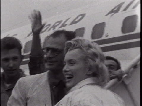 marilyn monroe and husband arthur miller walk past photographers at idlewild airport as they depart for london. there is an opening wide shot of... - sailor stock videos & royalty-free footage