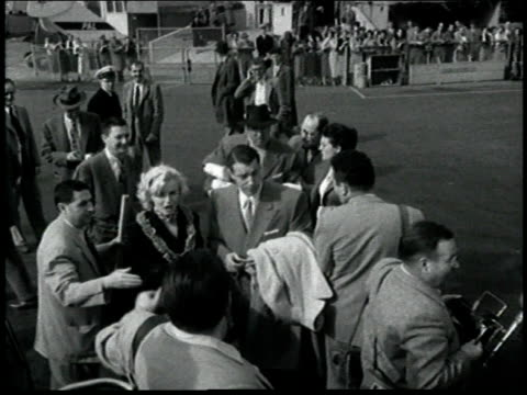 marilyn monroe and new husband joe dimaggio leave for their honeymoon in japan / they wave to fans before boarding airplane / frank o'doul manager of... - ハネムーン点の映像素材/bロール