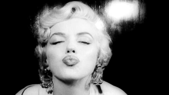 stockvideo's en b-roll-footage met marilyn monroe blows a kiss for the camera upon arriving at idlewild airport to work on the film the seven year itch marilyn monroe blows a kiss at... - kussen met de mond