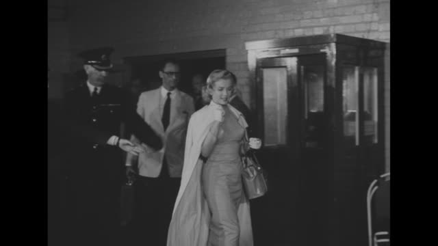 marilyn monroe, escorted by pilot and another man enters room for press conference, she is followed by arthur miller, camera flashes go off / three... - ローレンス オリビエ点の映像素材/bロール