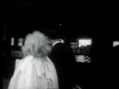 vídeos de stock e filmes b-roll de marilyn monroe gets out of car and joins husband, arthur miller / they walk through train station and board train marilyn monroe and arthur miller on... - 1957