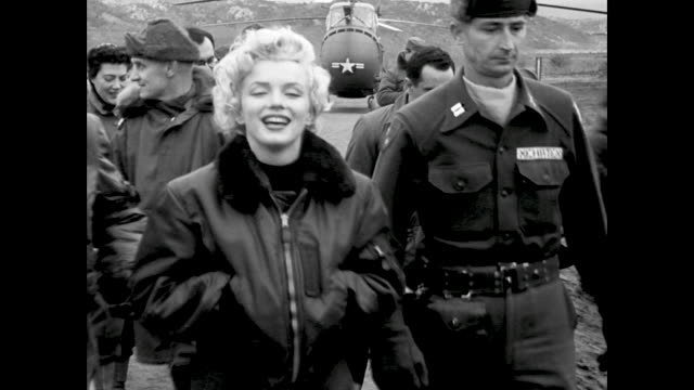 Marilyn Monroe getting out of helicopter greeted by Brigadier General Lionel McGarr and others Marilyn gets into a staff car and talks through open...