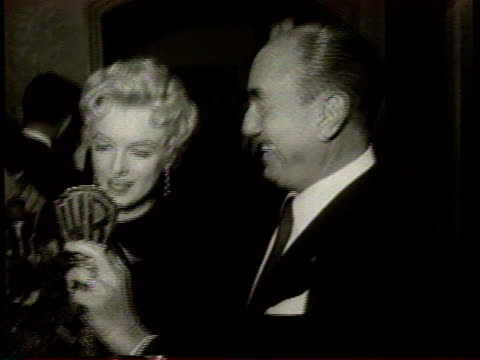 marilyn monroe is greeted by cheering people / she receives a warner bros key and a large bouquet of flowers from jack warner / marilyn monroe speaks... - warner bros stock videos & royalty-free footage