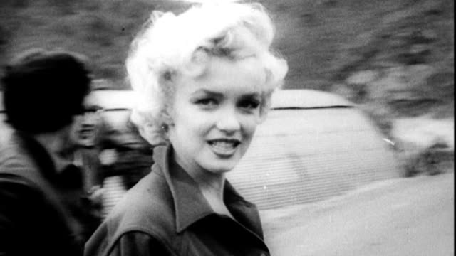 stockvideo's en b-roll-footage met marilyn monroe is helped out of jeep by us troops / she smiles for the cameras marilyn monroe arrives in korea to support troops on february 18 1954... - marilyn monroe