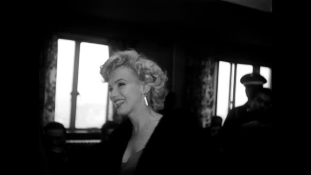 / marilyn monroe posing for a photographer / shaking hands with men seated in dressing gowns / cu marilyn smiling marilyn monroe visits tokyo army... - examination gown stock videos & royalty-free footage