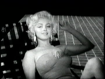 vidéos et rushes de marilyn monroe sitting in lawn chair drinks from glass then sexily talks to camera, saying, `i hate a careless man'. marilyn monroe talking to camera... - 1955