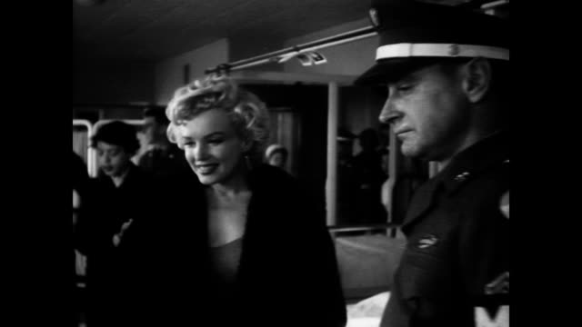 Marilyn Monroe visiting injured soldiers in hospital / speaks with man who is upside down in traction / shakes hands with young children in hospital...