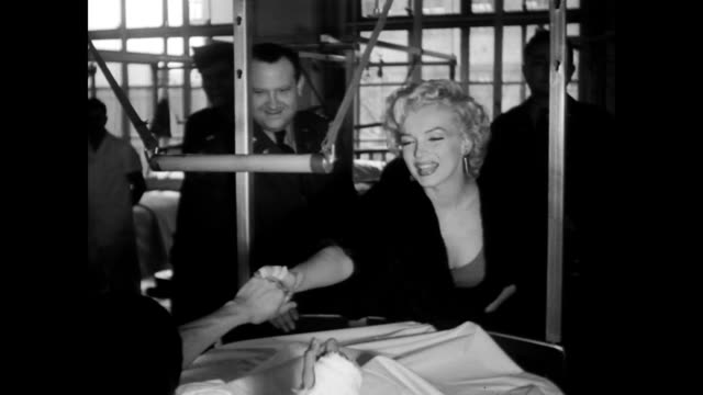 Marilyn Monroe visits Tokyo Army Hospital / Monroe smiling holding hands with bedridden soldier with press and staff in the background / CU Monroe...