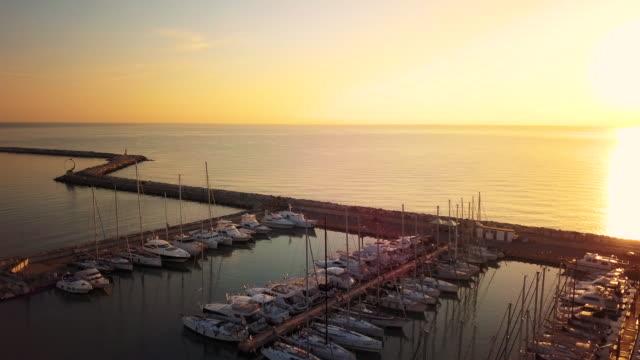 vídeos de stock e filmes b-roll de marina bay with sailboats and yachts in early morning - marina
