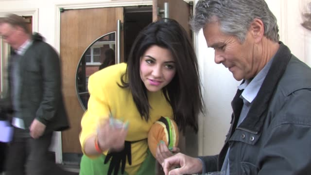 Marina Lambrini dressed as a sweetcorn and holding a fake burger at the Celebrity Sightings in London at London England