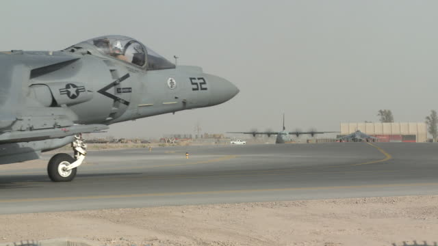 u.s. marine av-8b harriers taxi as a c-130 approaches from another direction. - marineinfanterie stock-videos und b-roll-filmmaterial
