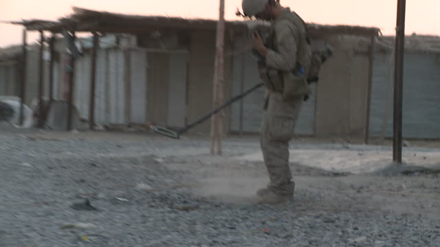 vídeos de stock, filmes e b-roll de a u.s. marine combat engineer uses a metal detector as he searches for ieds. - helmand
