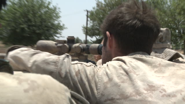 A U.S. Marine Corps scout-sniper gets information from his spotter as he sights his M40A3 sniper rifle.