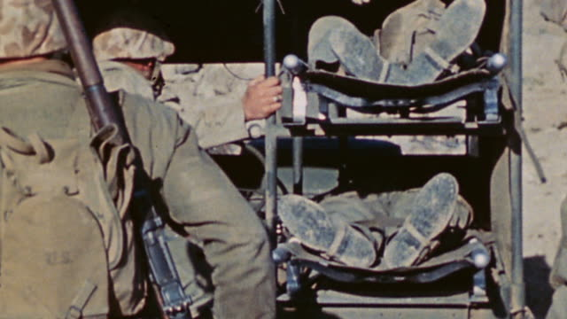 marine corpsmen loading casualties into jeep ambulance corpsman joining them in back and jeep driving off over rough rocky terrain / iwo jima japan - battle of iwo jima stock videos and b-roll footage